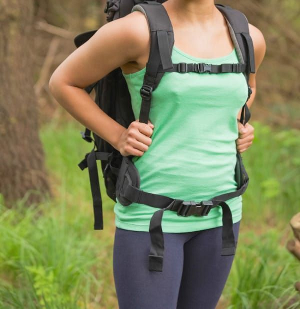 Pretty woman standing in a forest on a hike